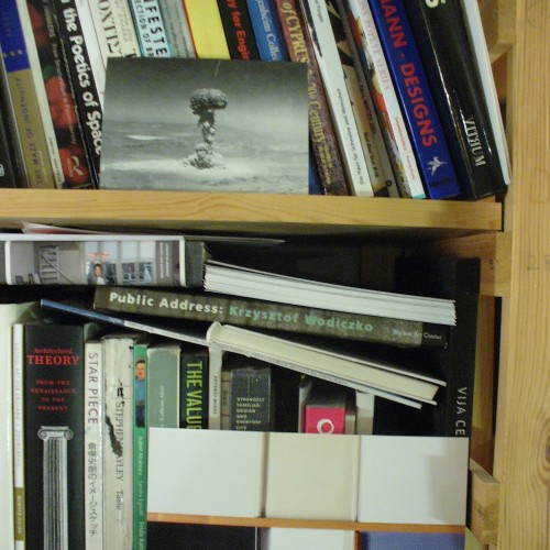 Bookshelf in studio displaying inspirational postcard