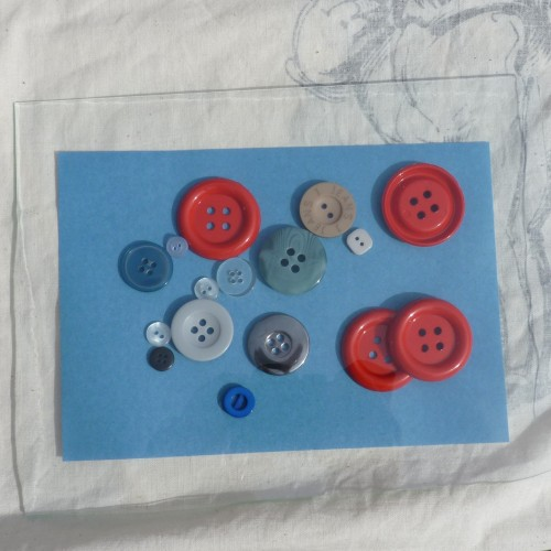 A selection of buttons on sun print paper under sheet of glass